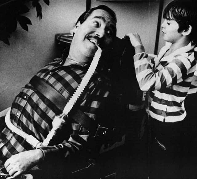 Photo of Ed Roberts sitting in his wheelchair with a tube in his mouth, looking at a young boy and smiling.