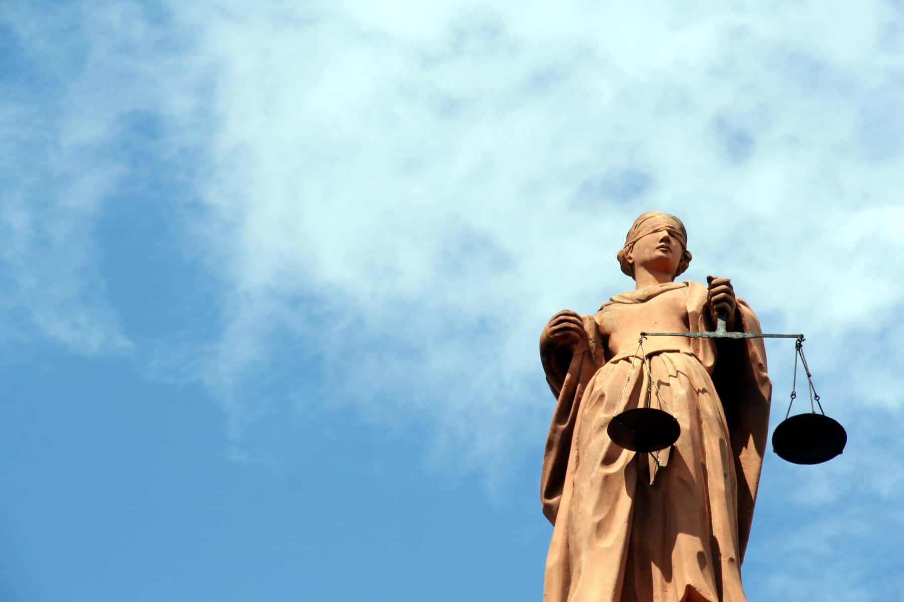 statue of lady justice, blindfolded, against a blue sky