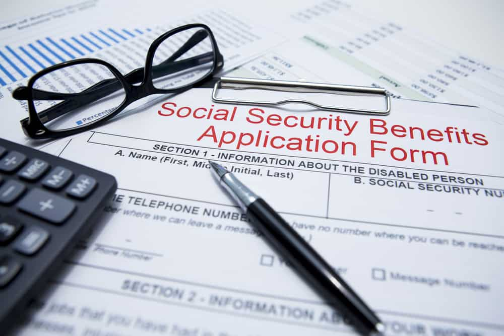 Social Security benefits application form, glasses, a pen and a calculator