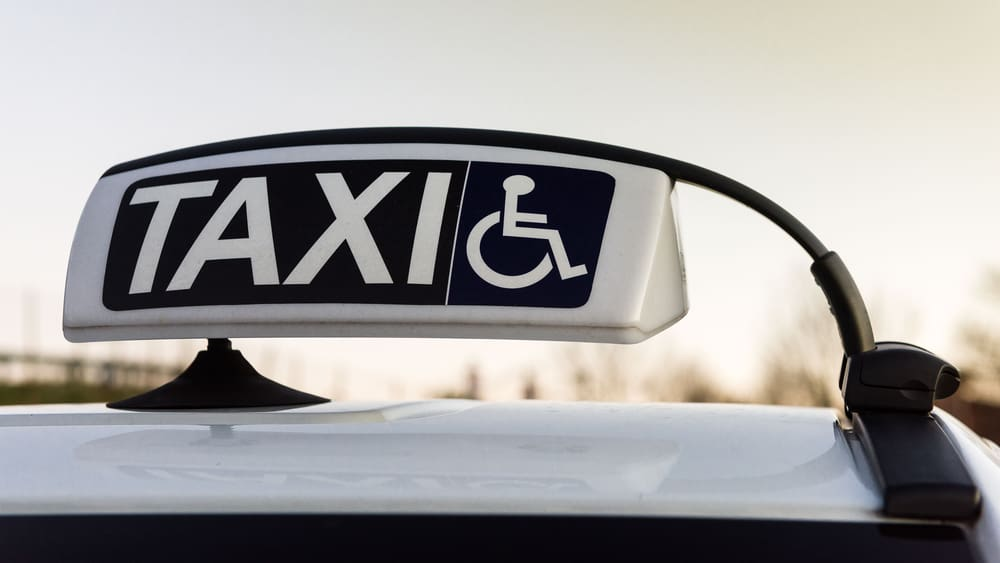 Taxi light on top of a car, with a universal accessibility logo