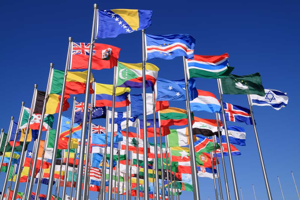 flags from many countries waving in the wind, blue sky in the background