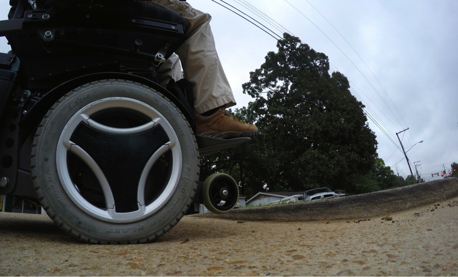 A photo looking at my wheelchair tires from ground level showing the scale of the problem.