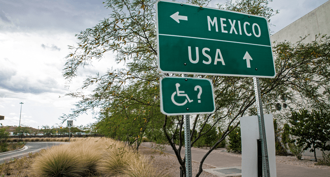 A road sign that reads Mexico with an arrow to the left, and USA with an arrow pointing forward.