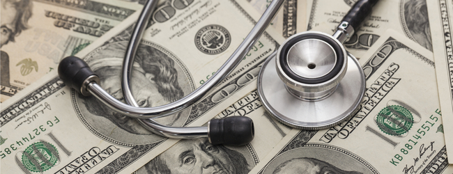 A photo of a stethoscope laying on top of a surface covered in U.S. hundred dollar bills