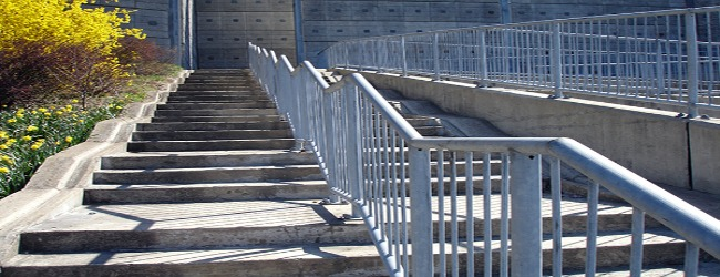 A wide cement staircase outside with a big metal railing in the middle.