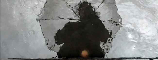 A darkened, unclear reflection of the top half of a person holding an umbrella, looking down at a grayish puddle of water.