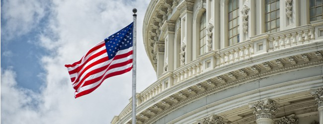 Part of the Capitol dome with the American flag waving in front of it. A blue cloudy sky in the background.