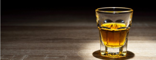 A single glass of whiskey sitting on a wood table.