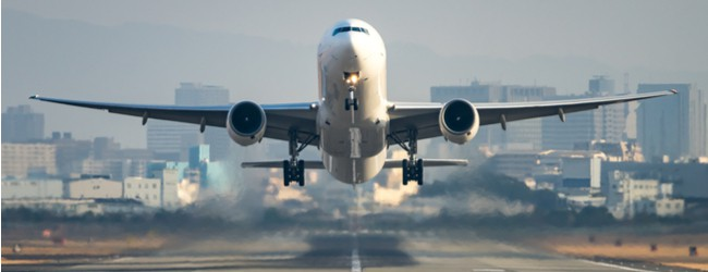 Photo of an airplane hovering over a runway, taking off.
