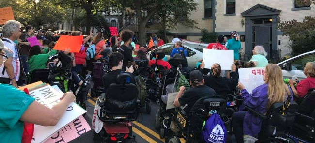 Large group of ADAPT members, many using various mobility devices, holding signs during an action.