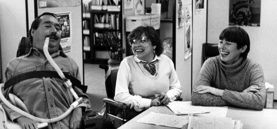 Ed Roberts and Judy Heumann in a black and white photo together, talking and smiling.